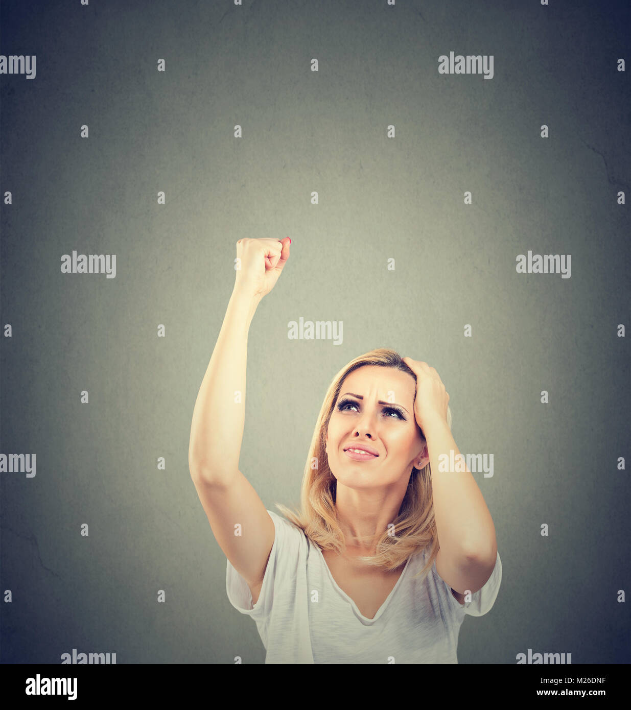 Casual woman threatening with fist while looking up disliking bad neighbors. - Stock Image