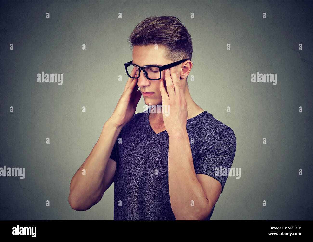 Young casual man in eyeglasses rubbing temples with eyes closed trying to remember information. - Stock Image