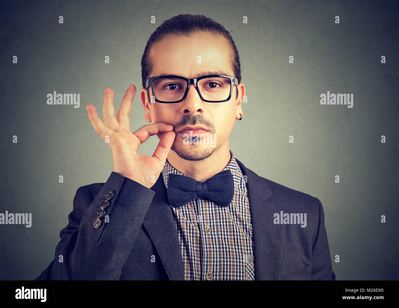 Confident serious man zipping mouth keeping confidential information while looking at camera. - Stock Image