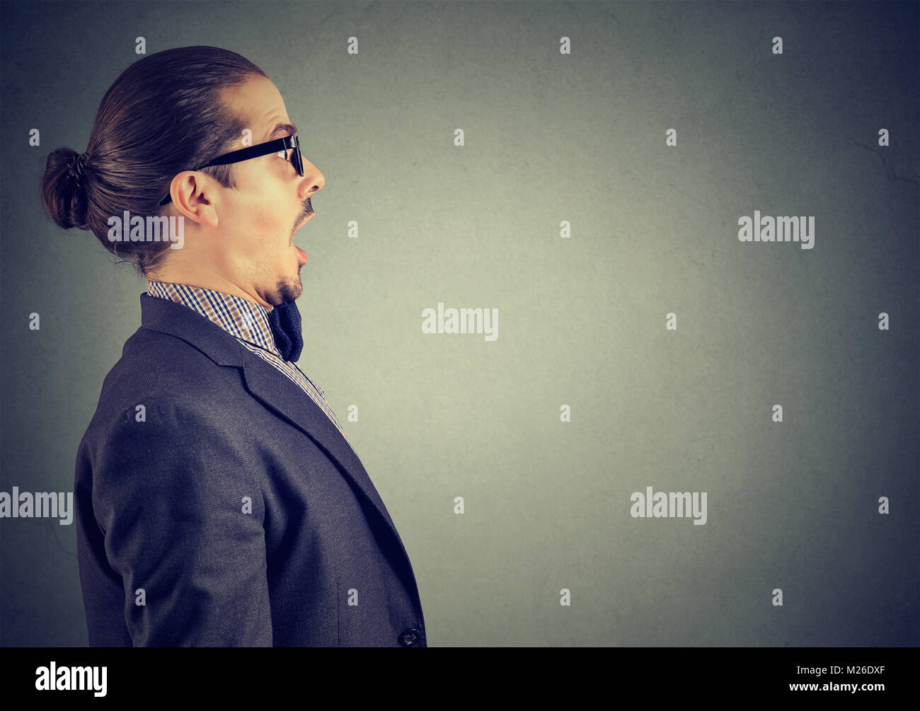Side view of man in suit standing with mouth opened on gray looking amazed and shocked. - Stock Image