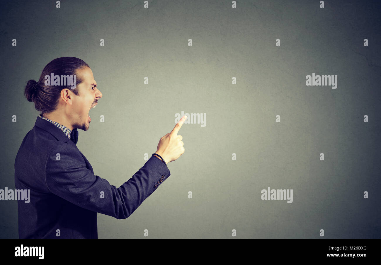 Side view of man in suit threatening with finger while shouting loudly and looking away. - Stock Image