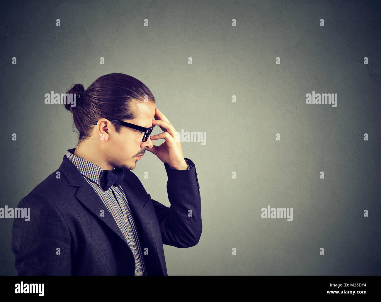 Concentrated man in suit rubbing forehead while brainstorming†pensively and looking away on gray backdrop. - Stock Image