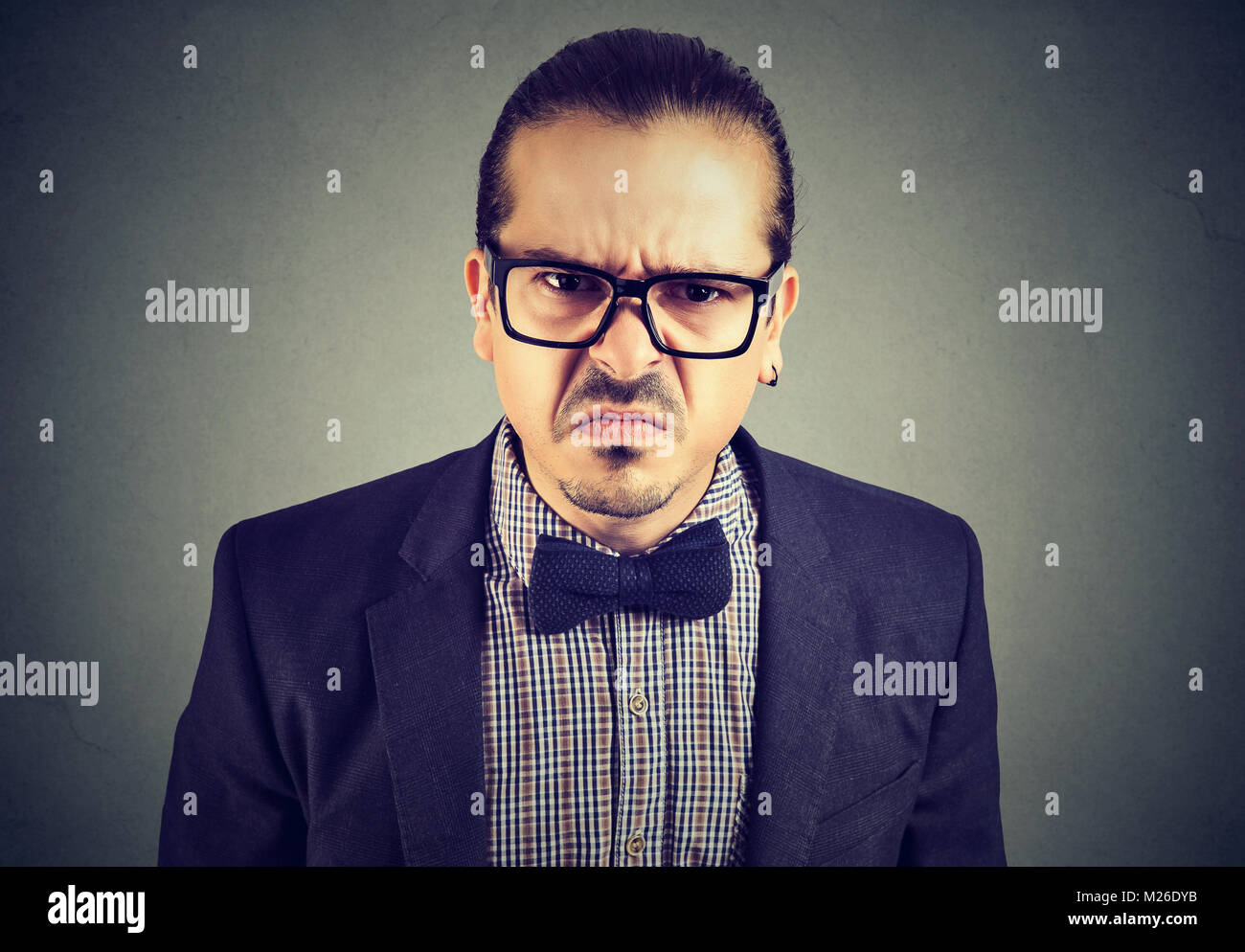 Portrait of young man looking dissatisfied at camera with grumpy facial expression. - Stock Image