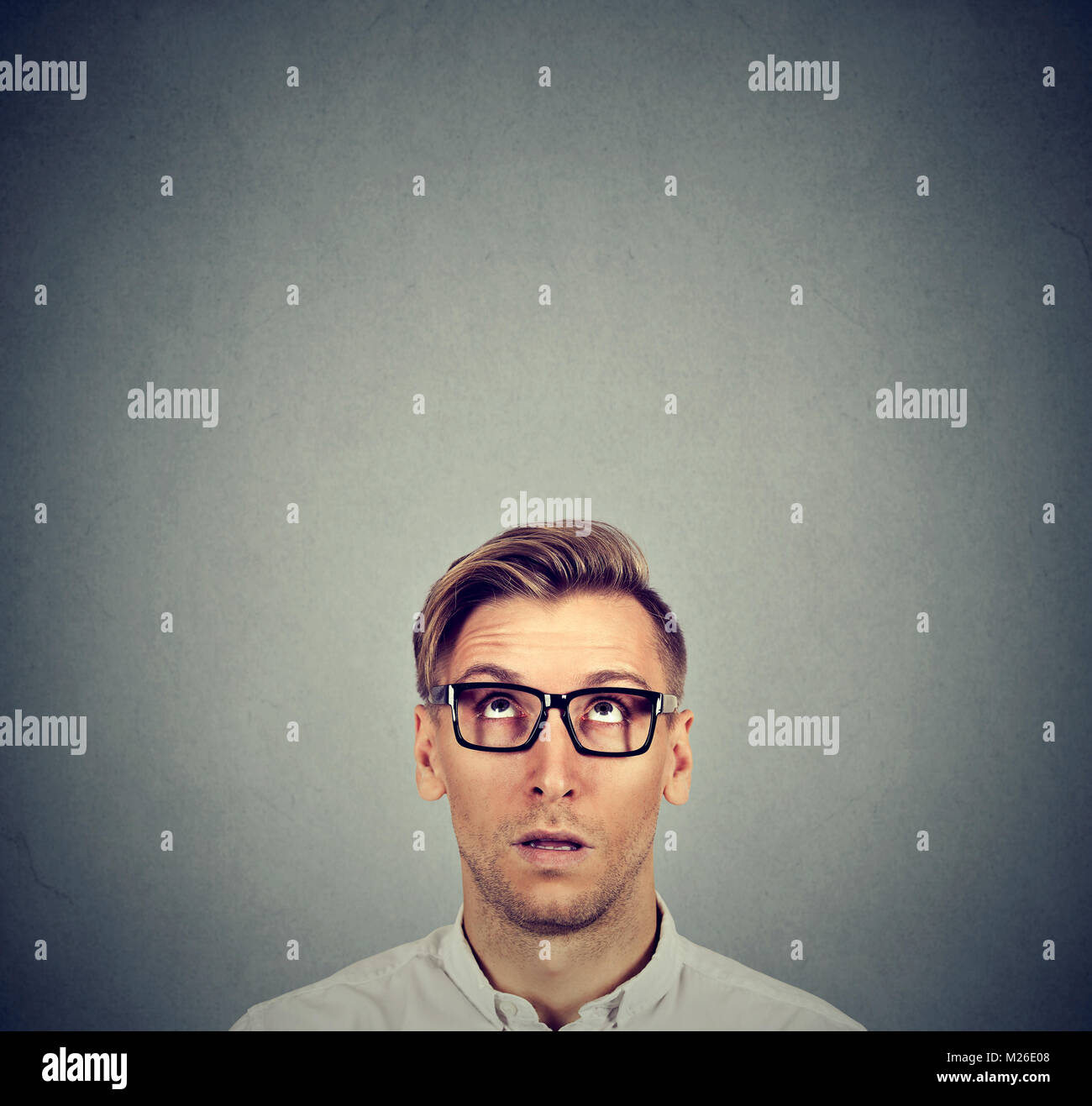 Young man in eyeglasses looking up posing on gray with expression of perplex. - Stock Image