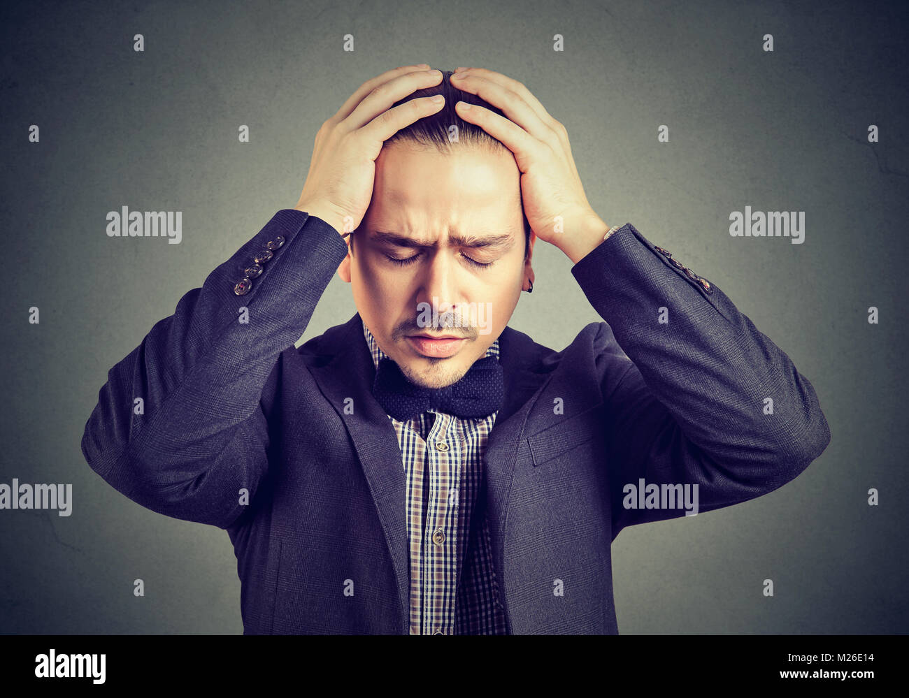 Young businessman in suit holding hands on head looking desperate. - Stock Image