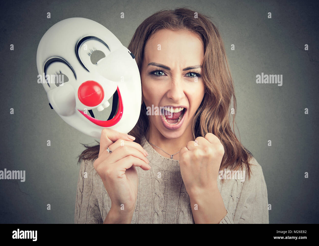 Young woman holding clown mask and screaming at camera on gray. - Stock Image