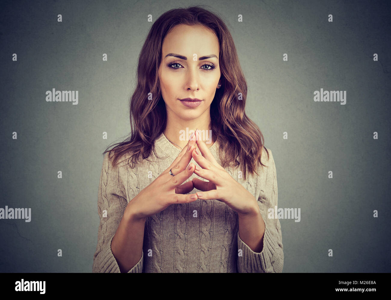 Young sly woman holding hands together spinning intrigues and looking cunning. - Stock Image