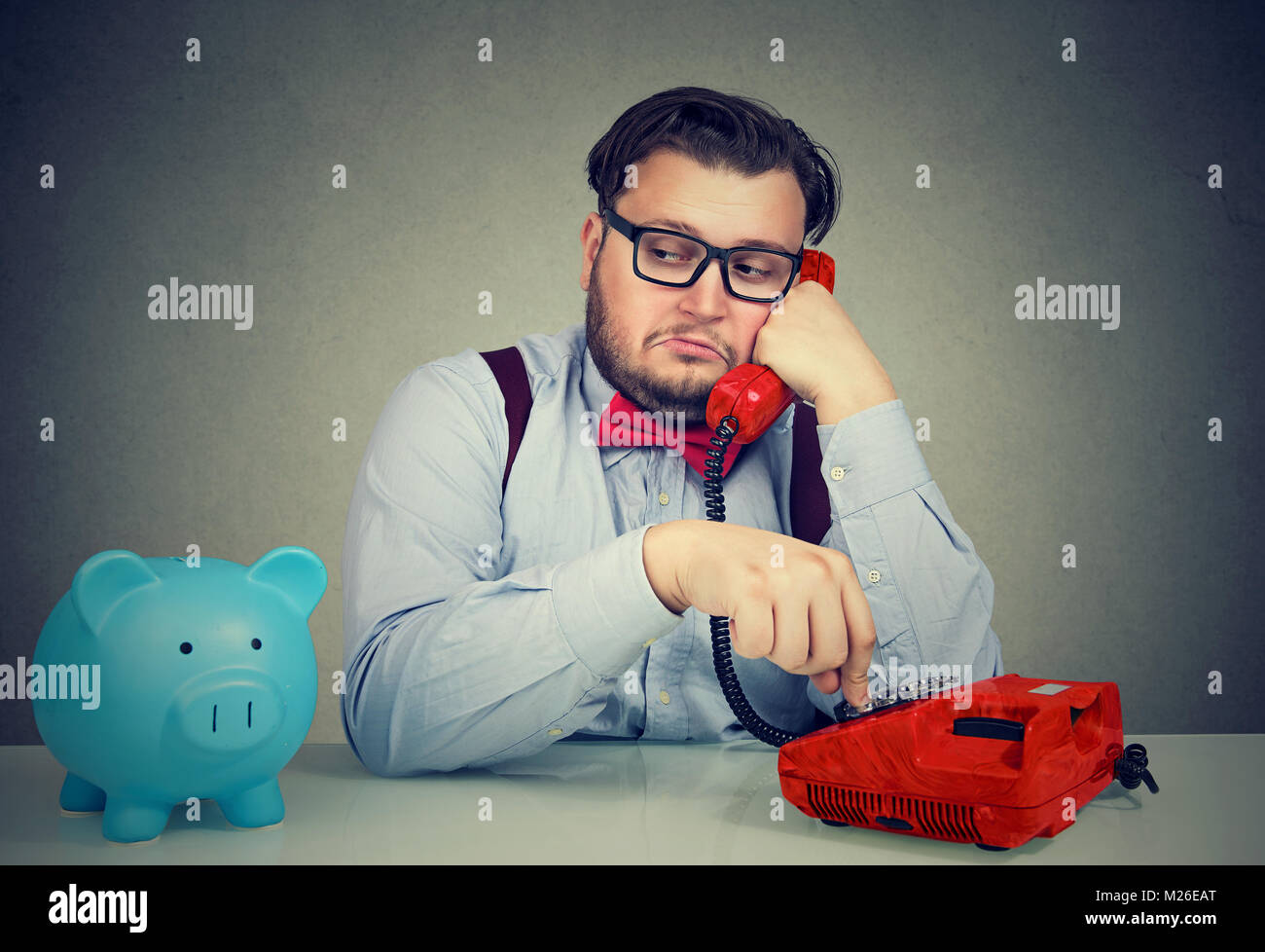 Sly young business man sitting at desk with moneybox and talking on phone callling a client. - Stock Image