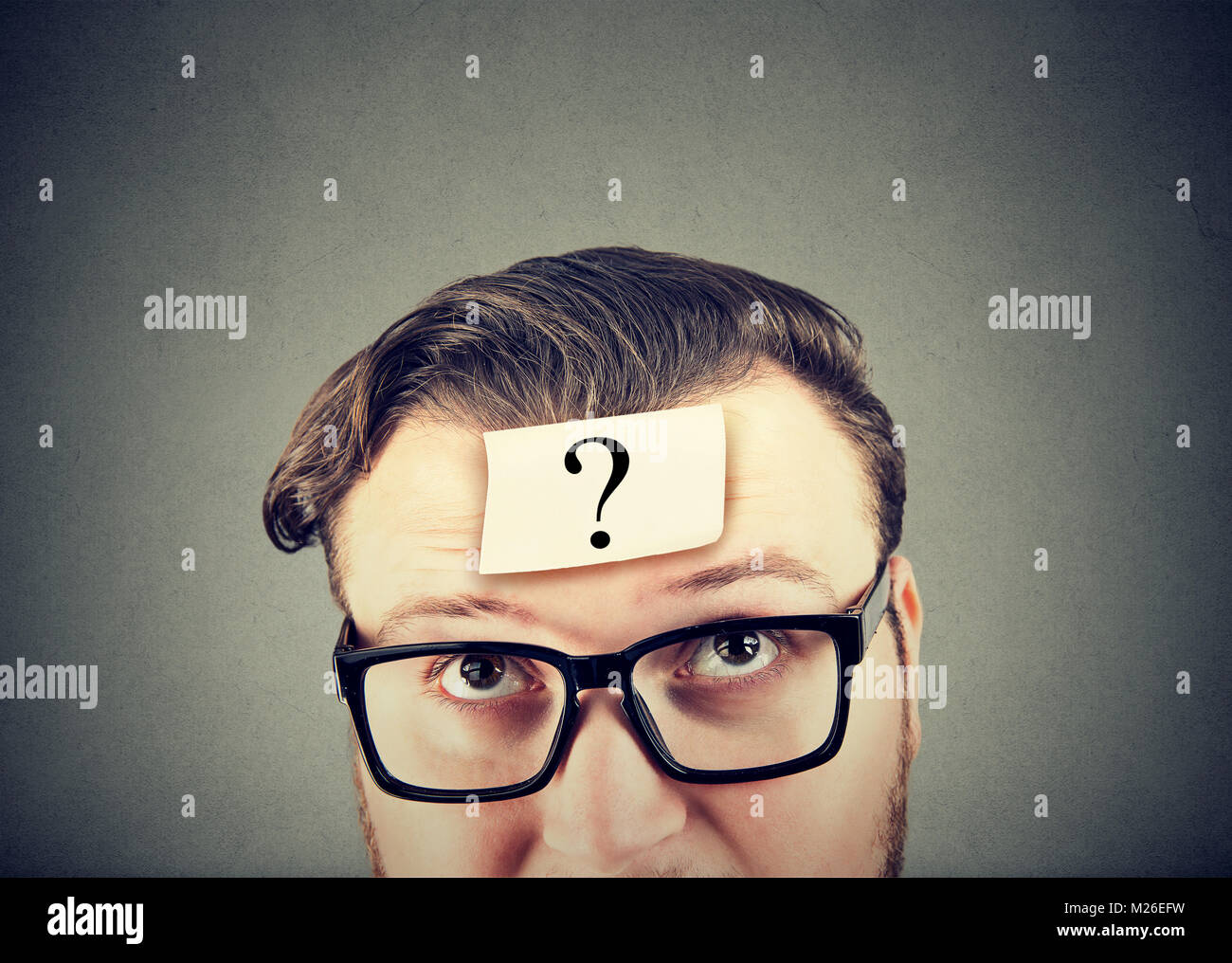Young man in eyeglasses having question in mind looking perplexed. - Stock Image