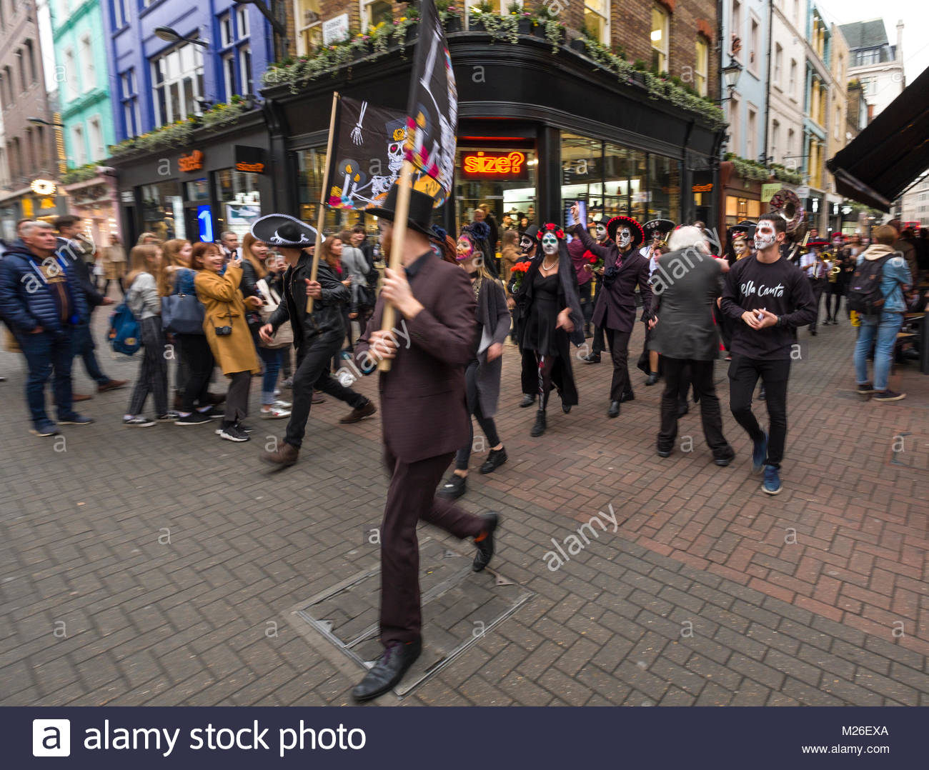 Small parade of people and musicians wearing makeup to make their faces look like skulls along the Carnaby Street - Stock Image