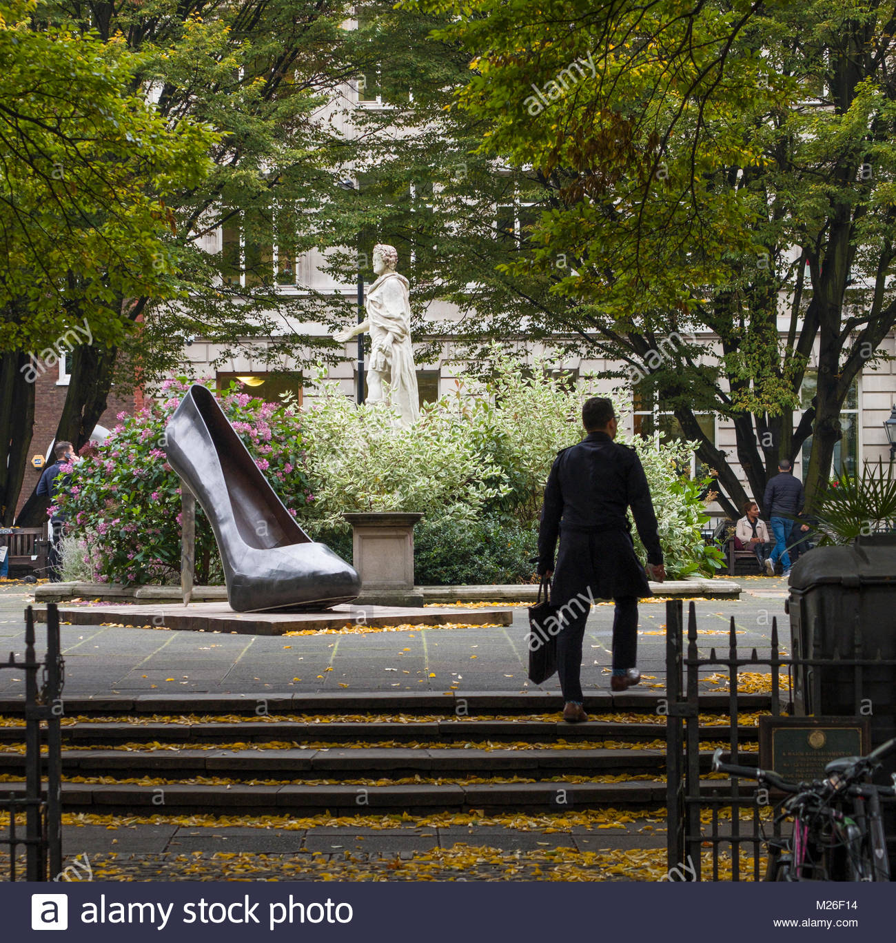 Man walking upstairs past Stiletto Heel sculpture by Kalliopi Lemos in Golden Square, City of Westminster, London, - Stock Image