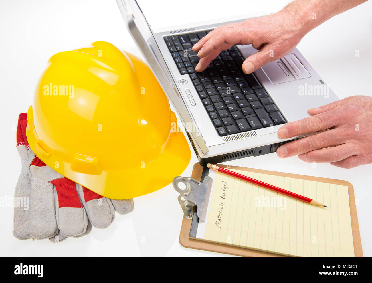 Highkey set with Helmet and blueprint plans on laptop - Stock Image