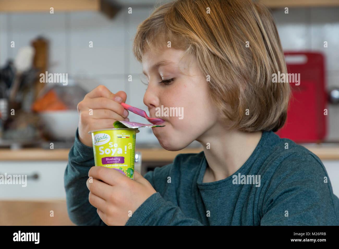Boy, 7 years old, tastes vegan food, soy fruit yogurt substitute, - Stock Image