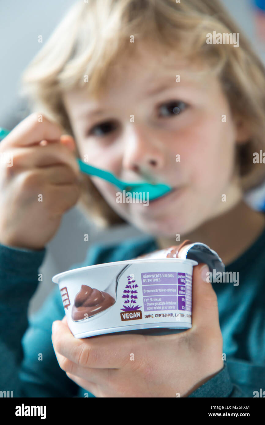 Boy, 7 years old, tastes vegan food, soy Chocolate pudding, substitute, - Stock Image