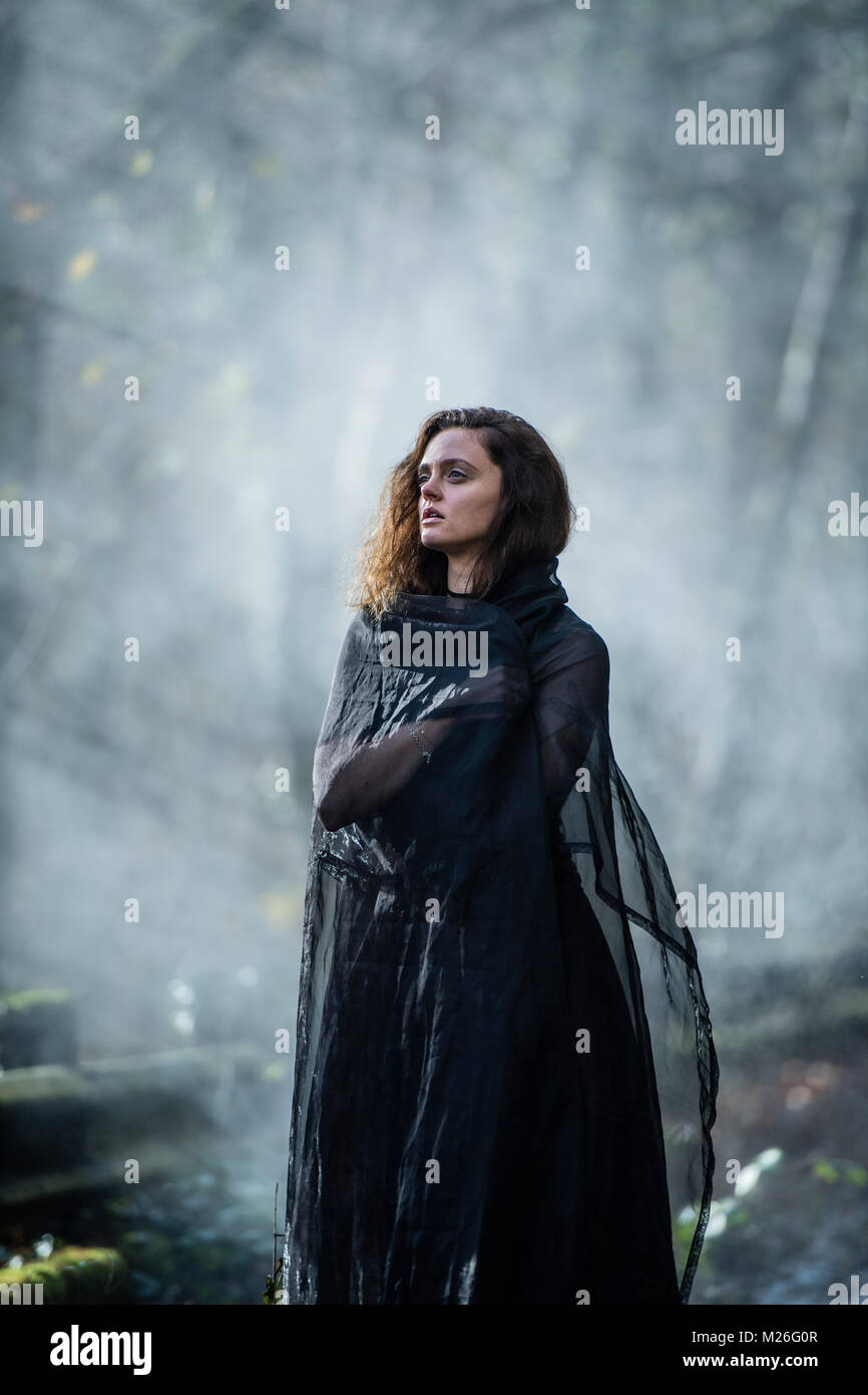 Woman of Mystery / Goth: A young woman model dressed in a black dress and cape, standing alone on a misty abandoned - Stock Image
