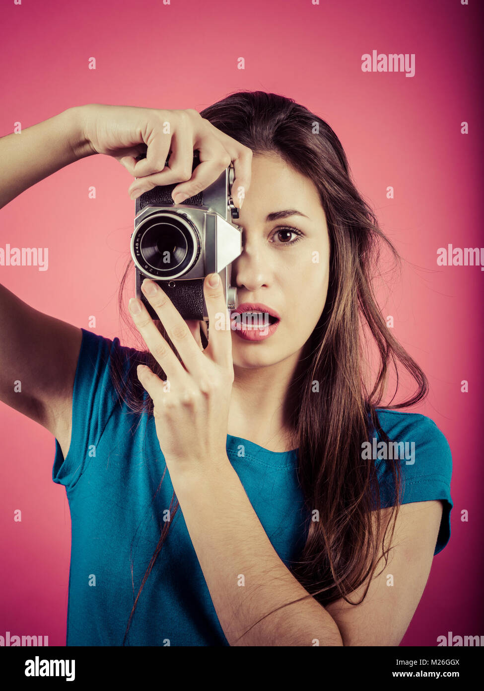 Photo of a beautiful woman pointing a vintage camera with a surprised look on her face. - Stock Image