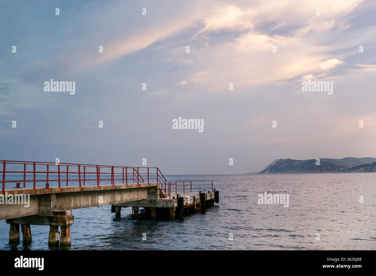 Close-up of the shipping pier on the sea at dawn. - Stock Image