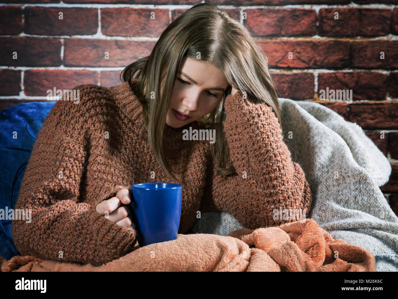 girl with a cup of tea sits wrapped in a rug Stock Photo