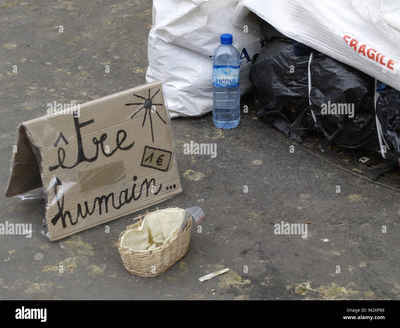 PARIS HOMELESS - ETRE HUMAIN ... - A MESSAGE ASKING SOME HELP NEAR THE SPOT OF A HOMELESS PERSON - PARIS MISERY - Stock Image