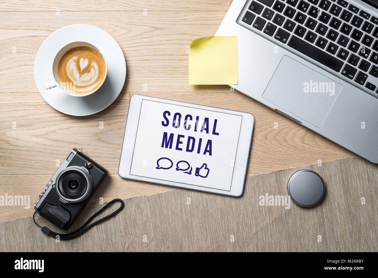 Social media writing with emoticons on tablet screen with camera, coffee mug and laptop lying on office desk as - Stock Image