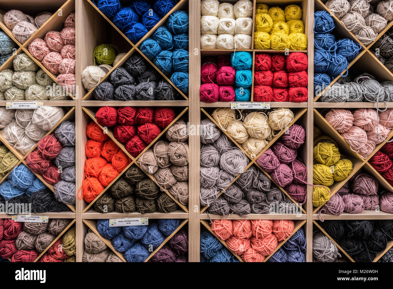 Skeins of wool in a rack - Stock Image