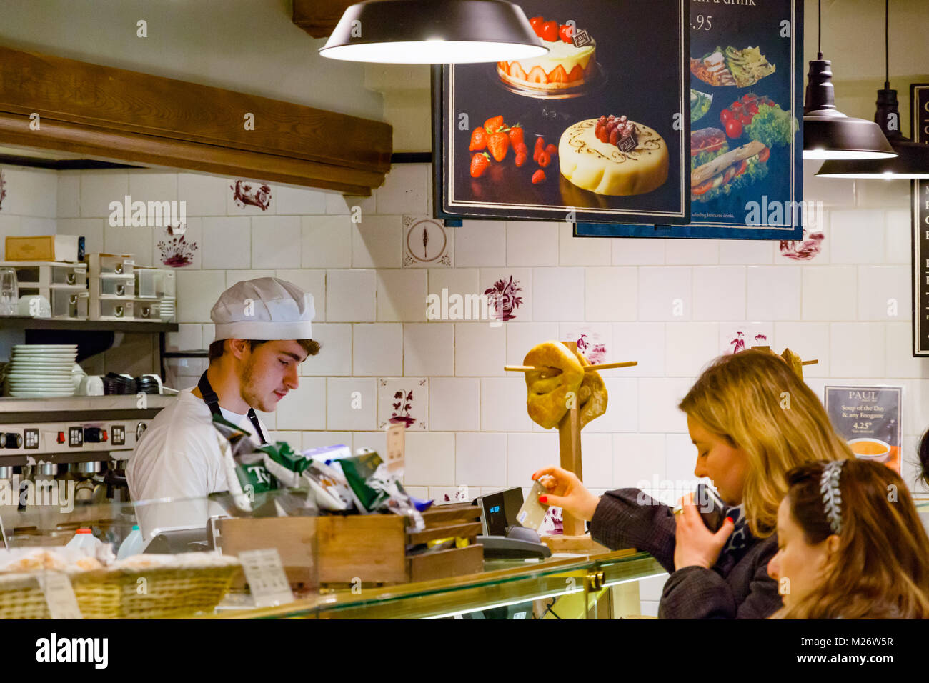 London, UK - February 25, 2018 - Staff servicing customers at Paul bakery shop in Canary Wharf - Stock Image