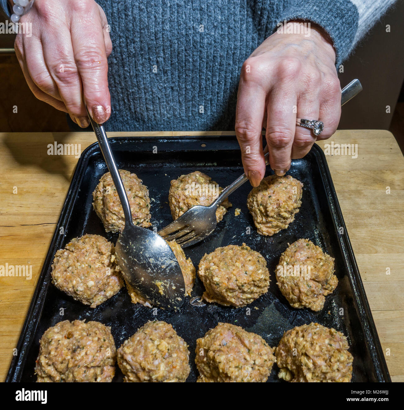 Woman's hands using a fork and spoon to arrange uncooked sausagemeat stuffing balls, in rows on a baking tray, ready - Stock Image