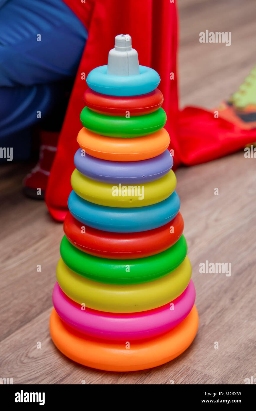 Colorful plastic rainbow toy pyramid for little kids on the blue background. Children's bright multi-colored toys. Stock Photo