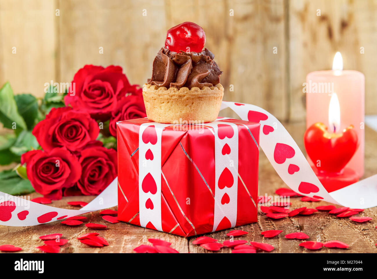 Cupcake with cherry over red gift box in front of bouquet of red roses and candles on wooden background. Valentines - Stock Image