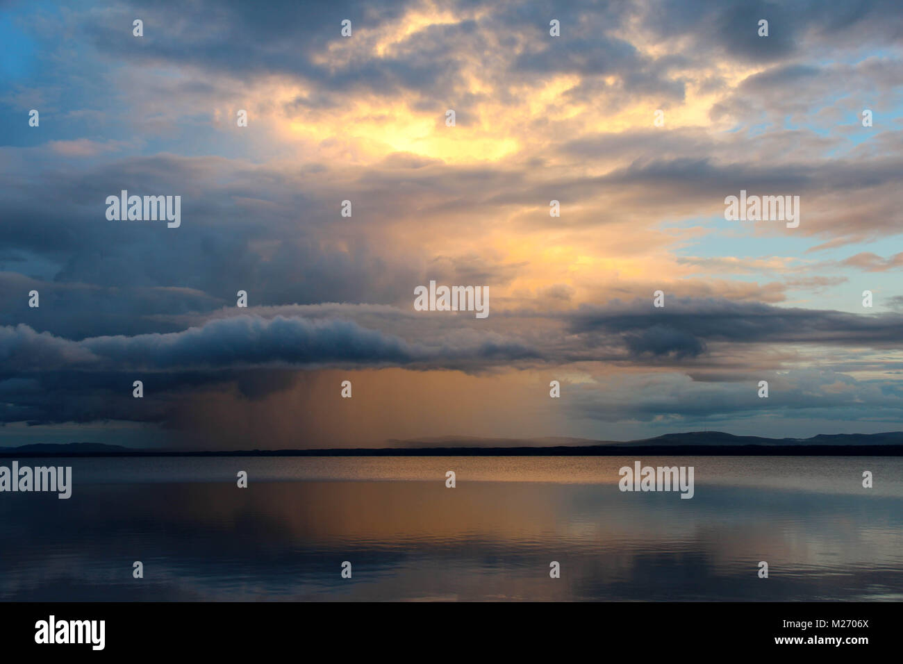 Sunset with colorful clouds and rain clouds over Orsa lake, Orsa, Dalarna, Sweden. - Stock Image