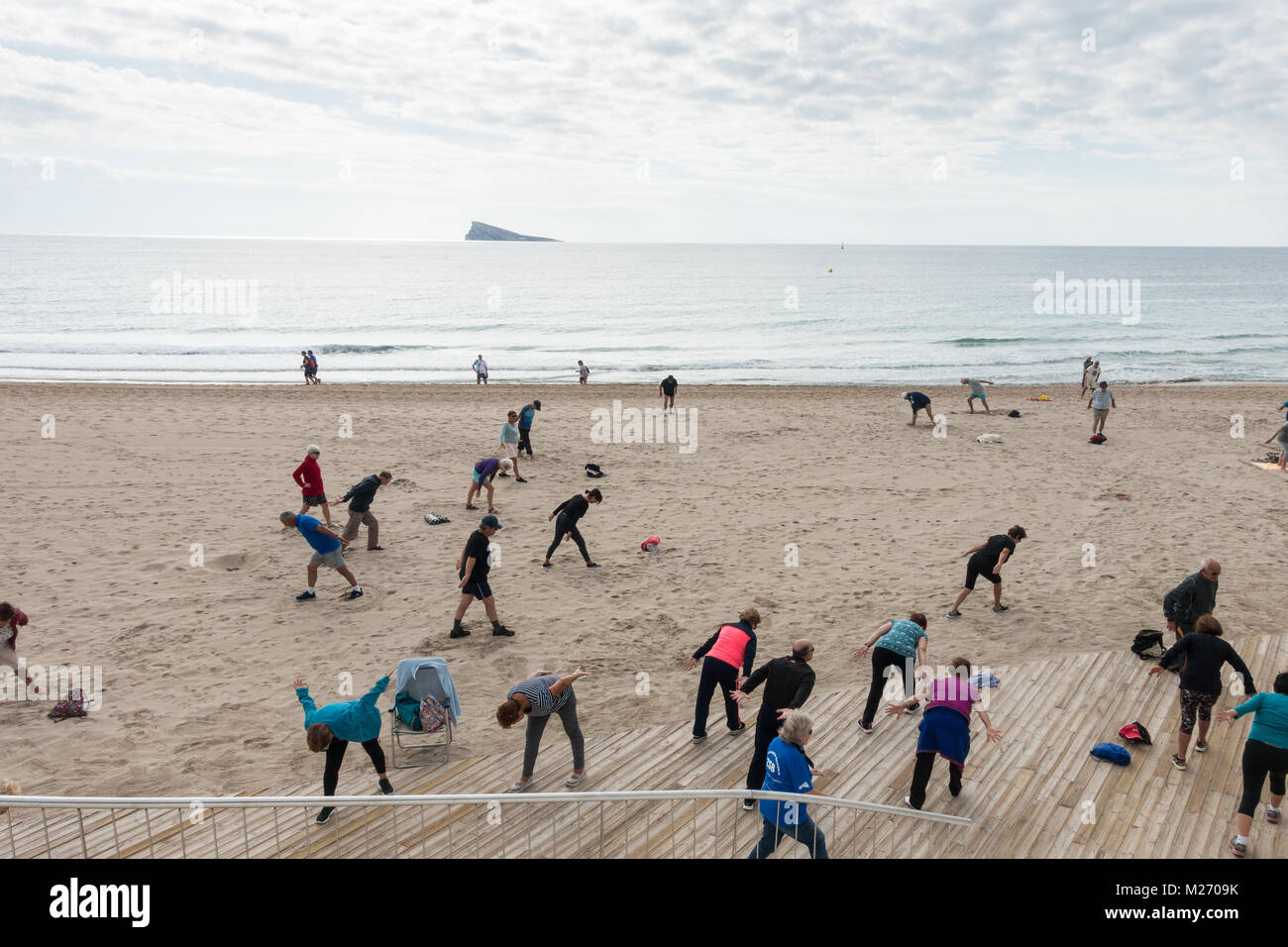 Seniors keeping fit on the beach in Benidorm, Spain. Men women oap's, elderly fitness class - Stock Image