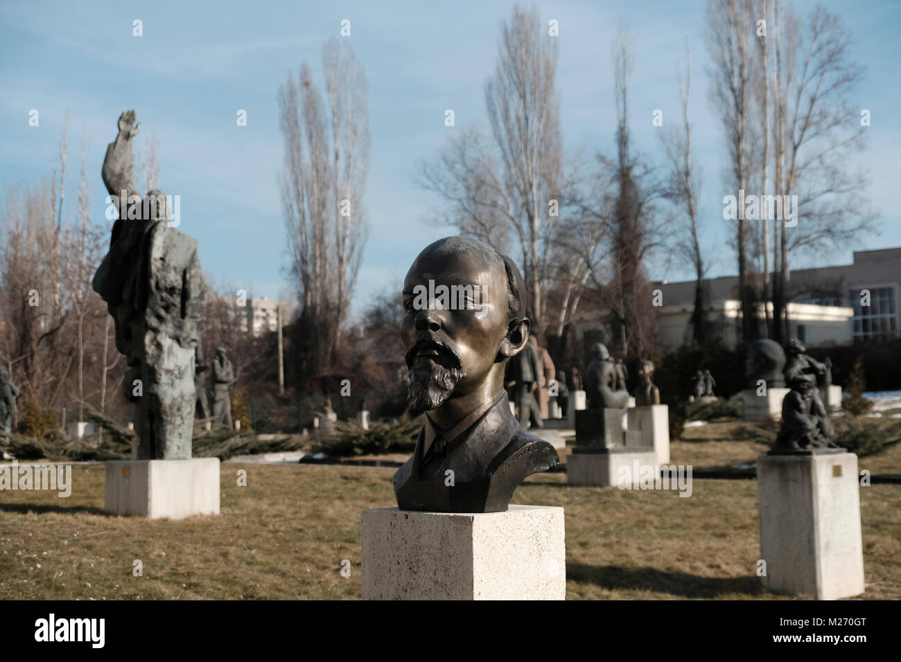 The bust of Vladimir Lenin stands amid sculpture installations drawn from the communist period in front of the Museum - Stock Image