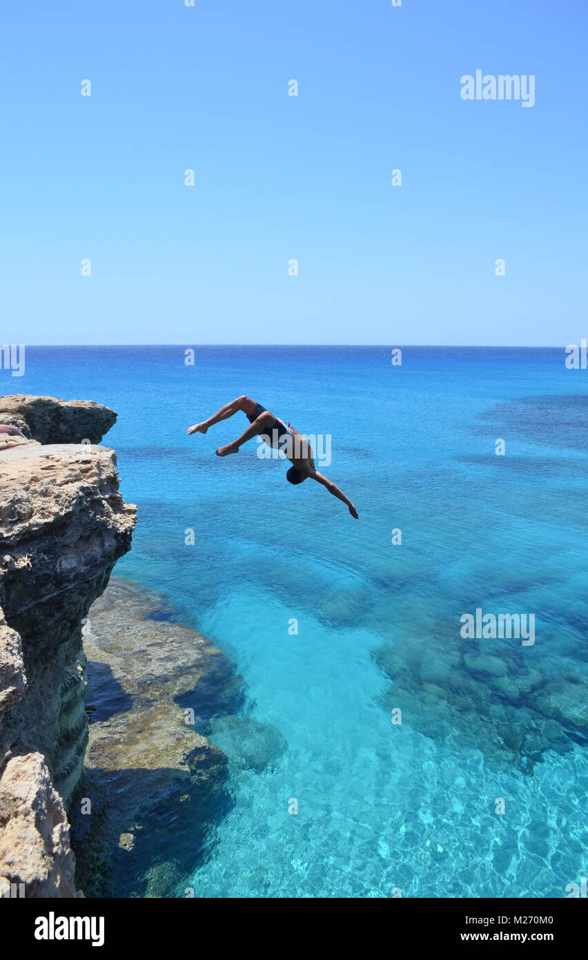 Brave man jumping off cliff into the Mediterranean Sea. - Stock Image