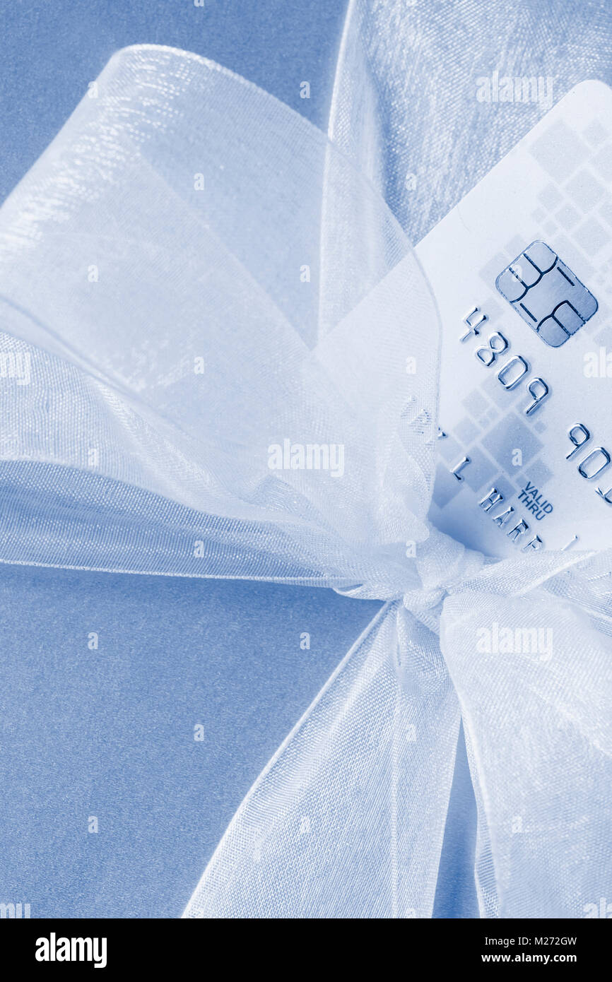 Close up of gift present with credit debit bank card showing security chip technology. Personal finance shopping - Stock Image