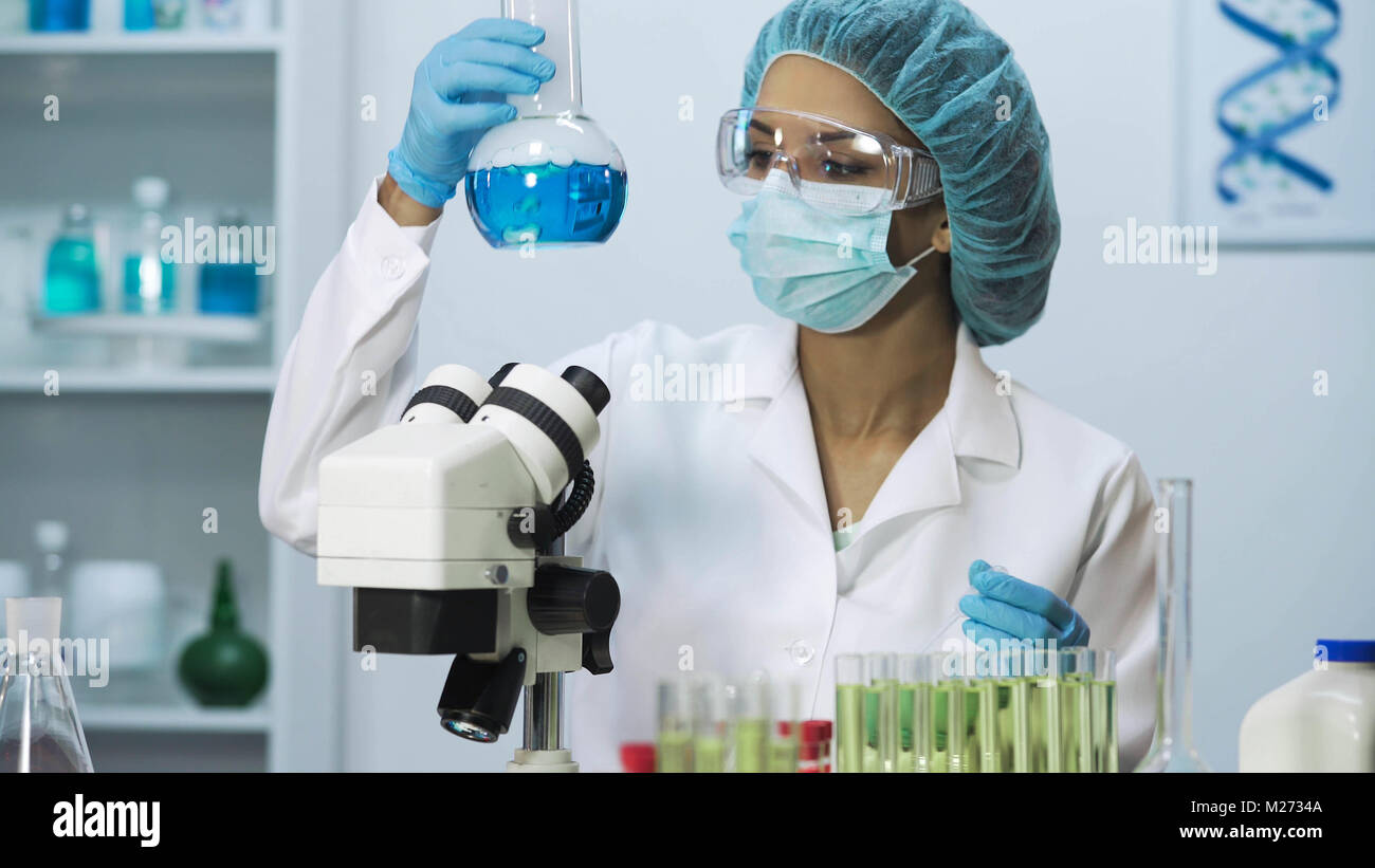 Biracial female scientist looking into microscope, doing biomedical research - Stock Image