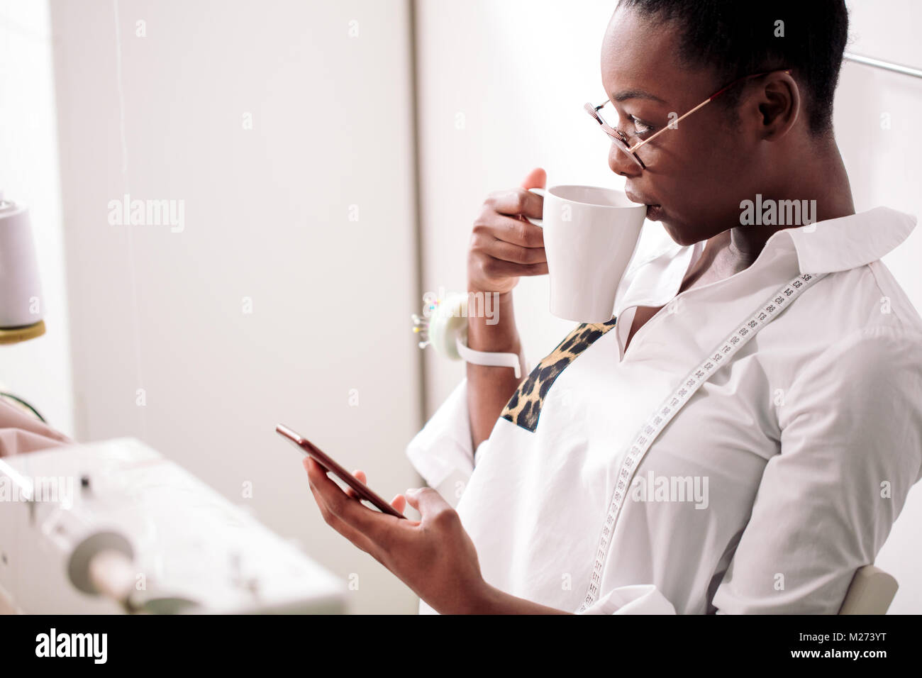 Cheerful woman seamstress in apron talking on phone and drinking coffee - Stock Image