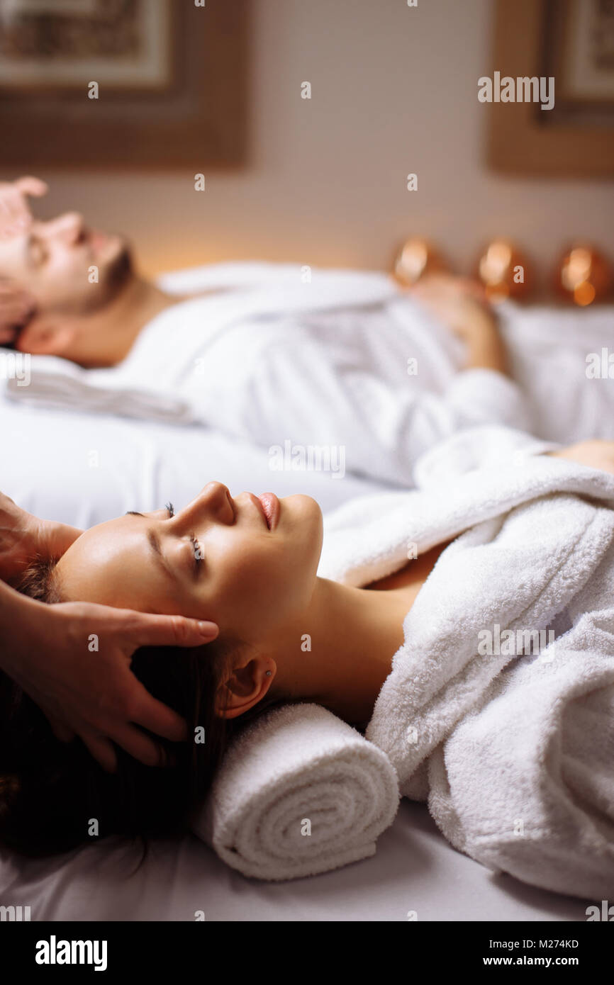 Young couple receiving head massage at beauty spa - Stock Image