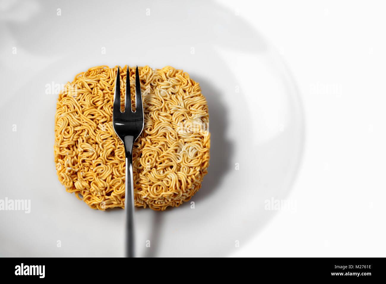 Asian instant noodles on a plate, Instant Nudeln, nicht zubereitet, auf einem Teller - Stock Image