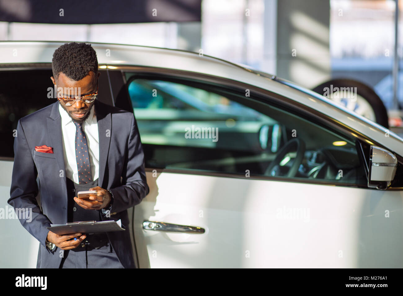 african car salesman using smart phone in showroom - Stock Image