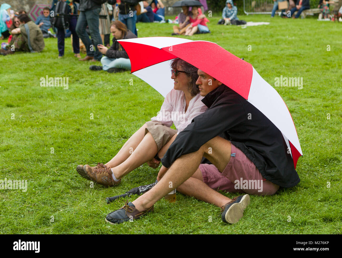 A couple in shorts shelter from the British summer weather under an umbrella whilst sitting on the grass at an outdoor - Stock Image