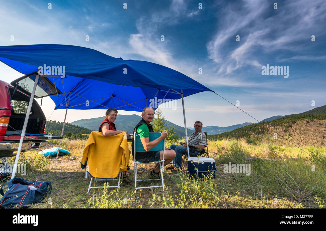 Middle aged campers at Brewer Creek Forest Service Road, Purcell Mountains, near Invermere, British Columbia, Canada - Stock Image