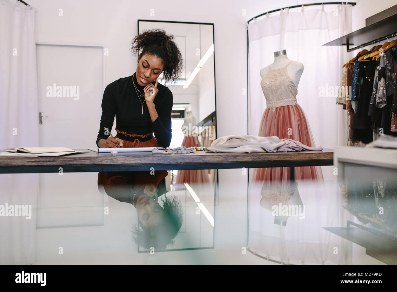 Female fashion designer sketching a design sitting at her table. Fashion entrepreneur engrossed in making a drawing - Stock Image