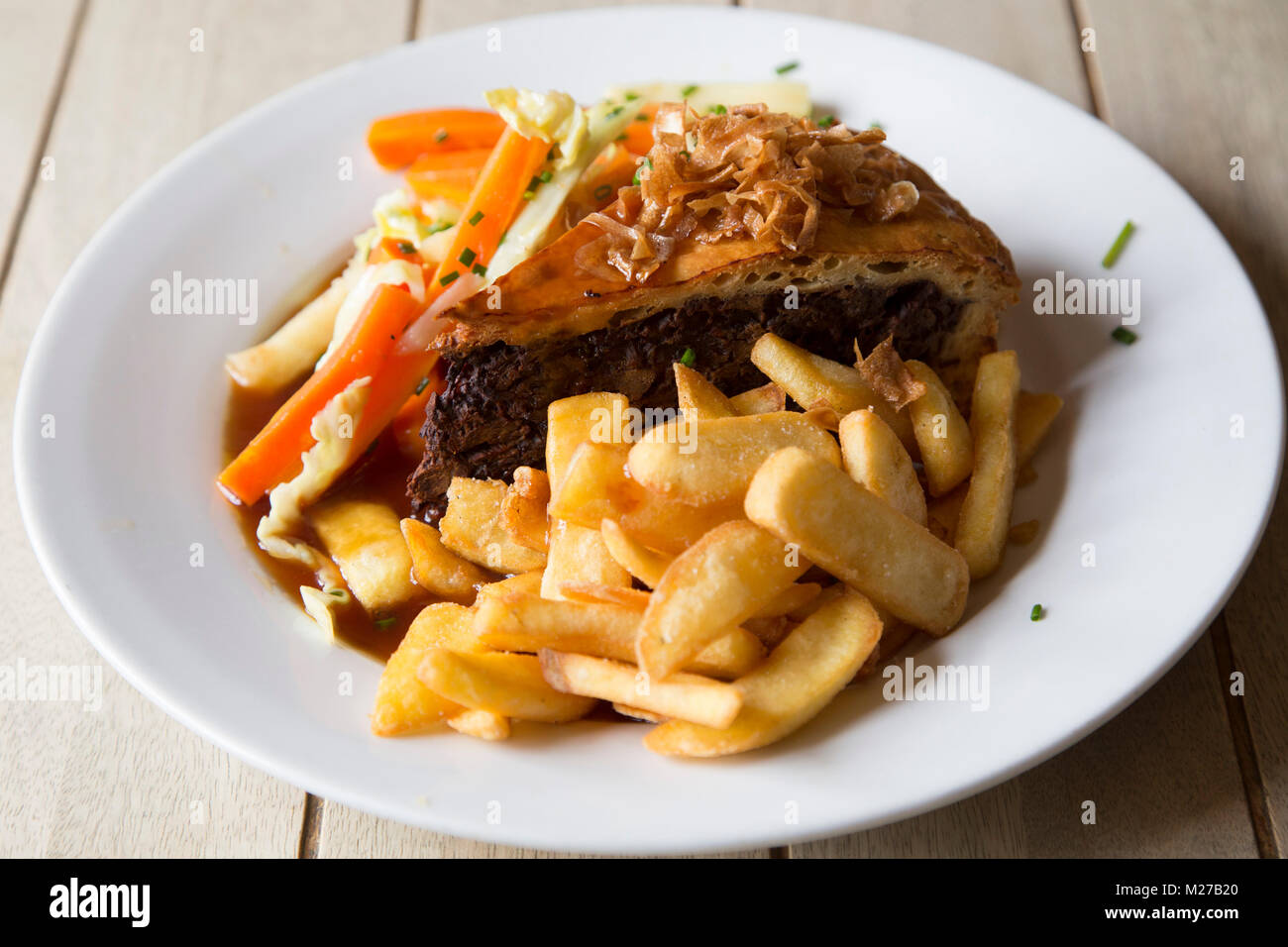 Steak and ale pie served with chips. The dish is a popular British pub meal. - Stock Image