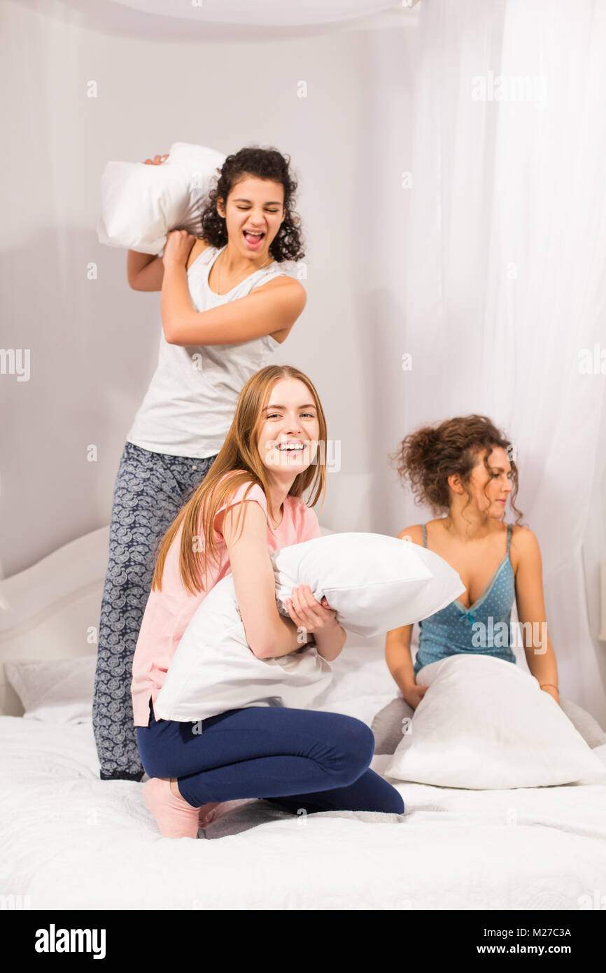 Girls in bed having pillow fight in pajamas - Stock Image