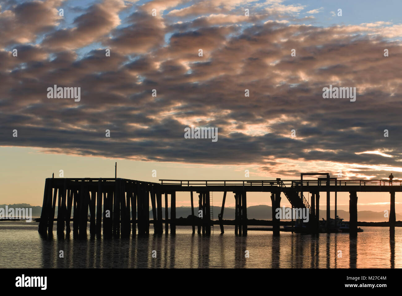 The dock at Kake, Kupreanof Island, in the Inside Passage of Southeast Alaska, in silhouette at sunset. - Stock Image