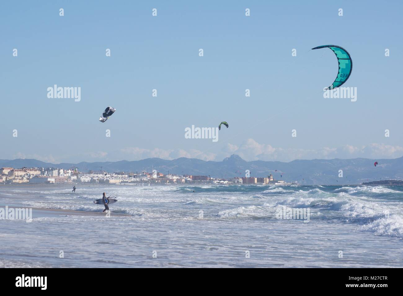 Kitesurfers at Los Lances beach with Tarifa and Morocco in the background - Stock Image
