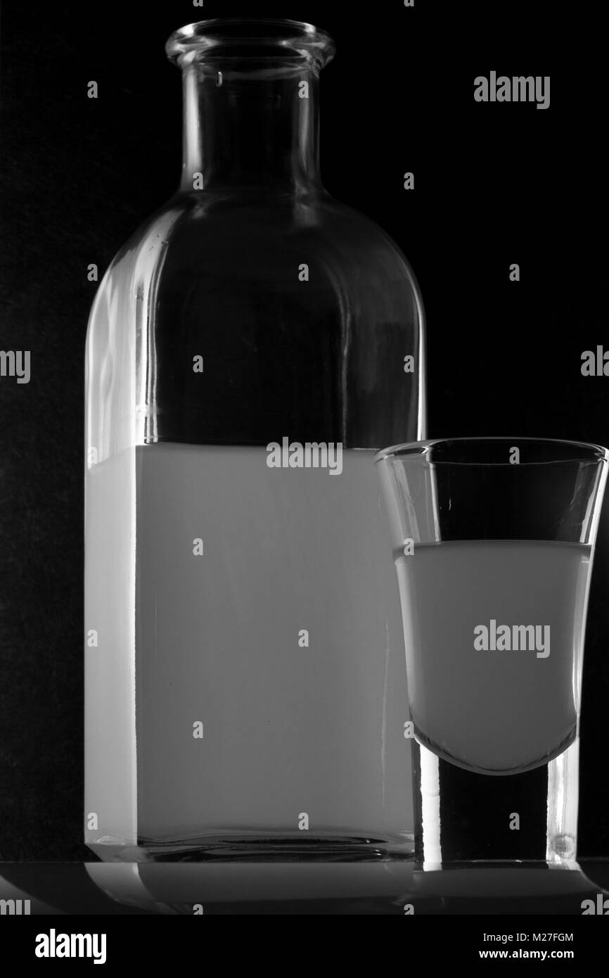 bank of moonshine and a glass on a black background - Stock Image