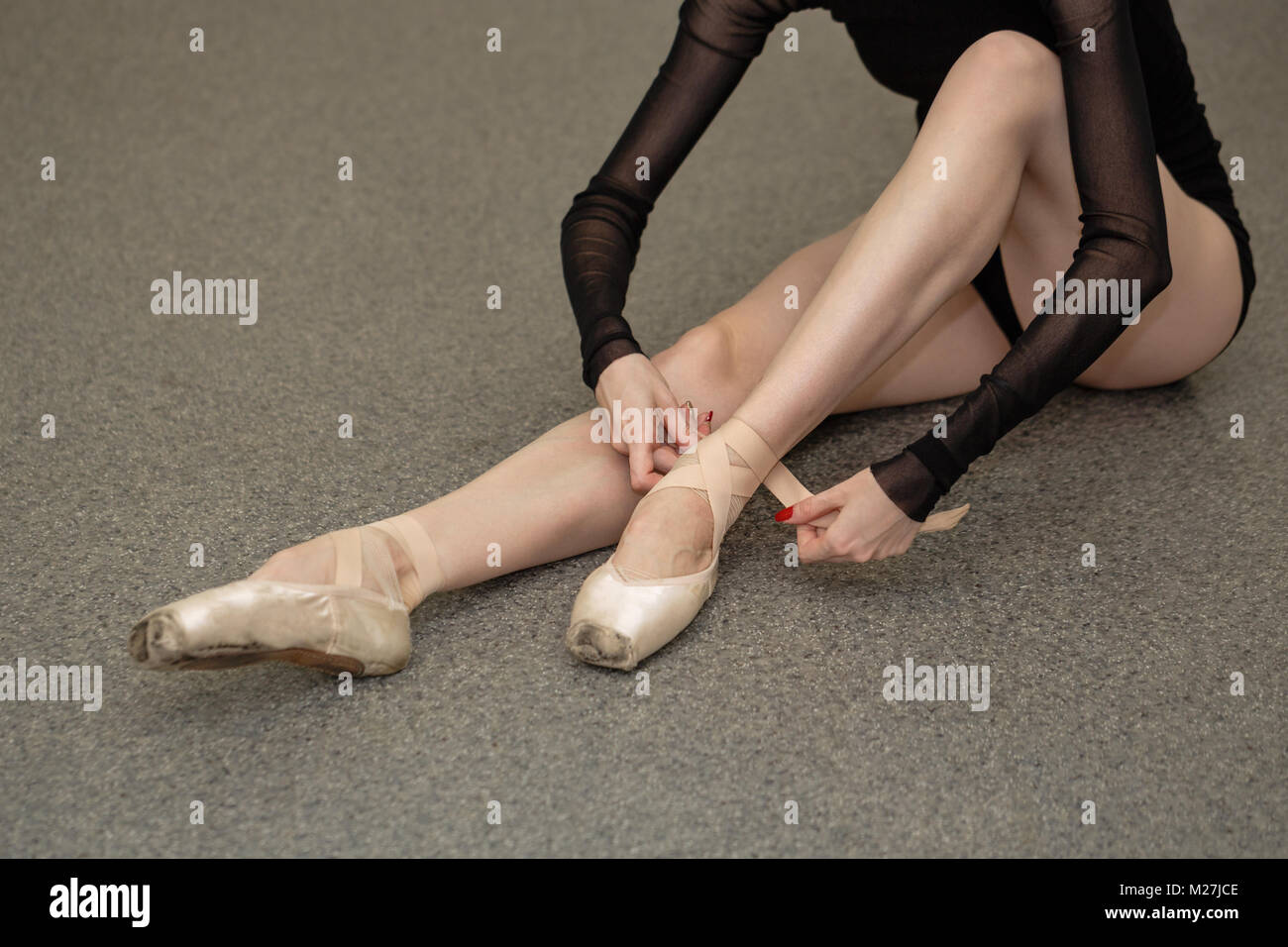 The ballerina ties the tapes with pointe shoes. Slender long female legs. Beautiful graceful hands. Shooting close - Stock Image