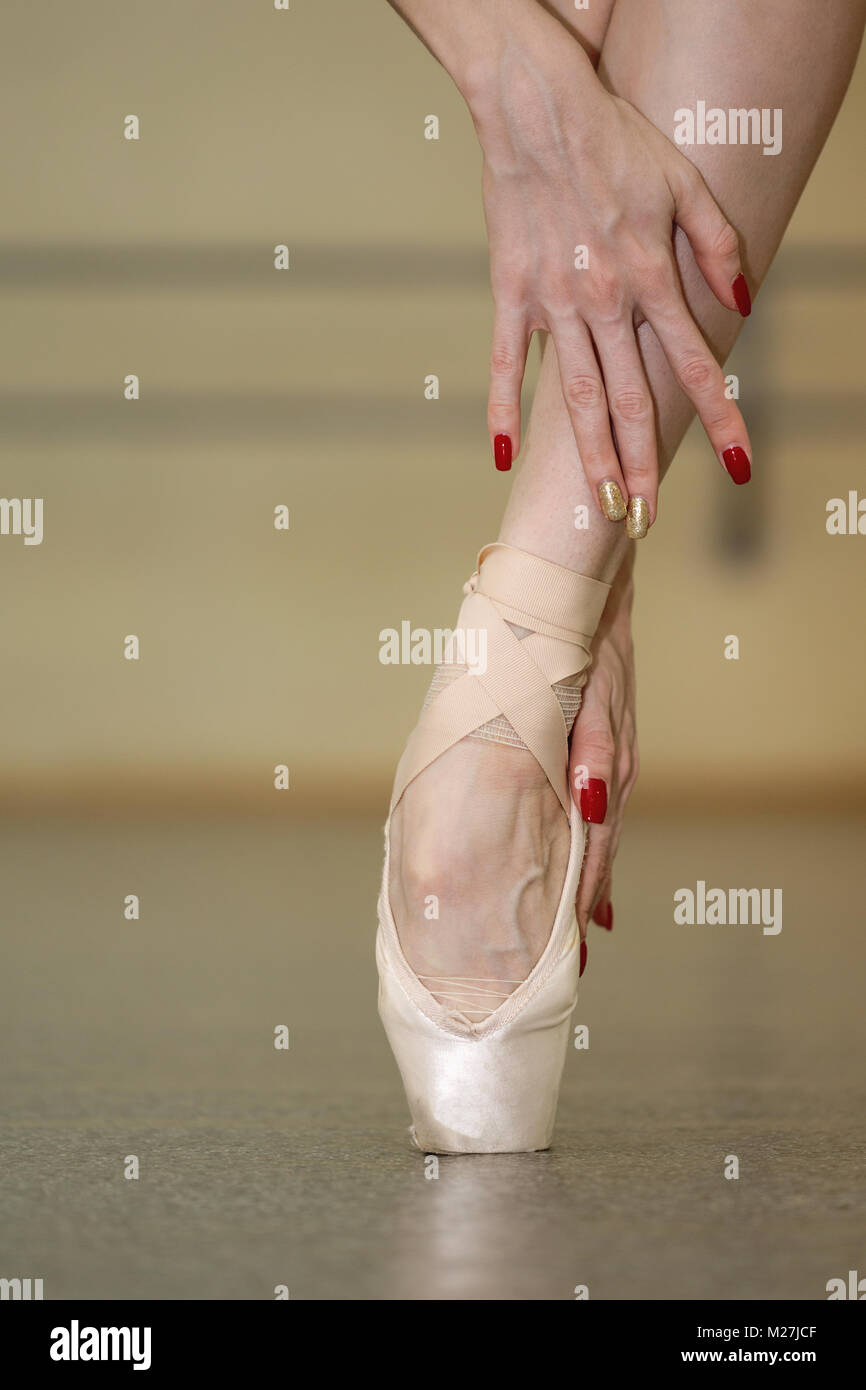 Leg of a ballerina in pointe. Beautiful graceful hands. Rehearsal dance on tiptoe. Close-up - Stock Image