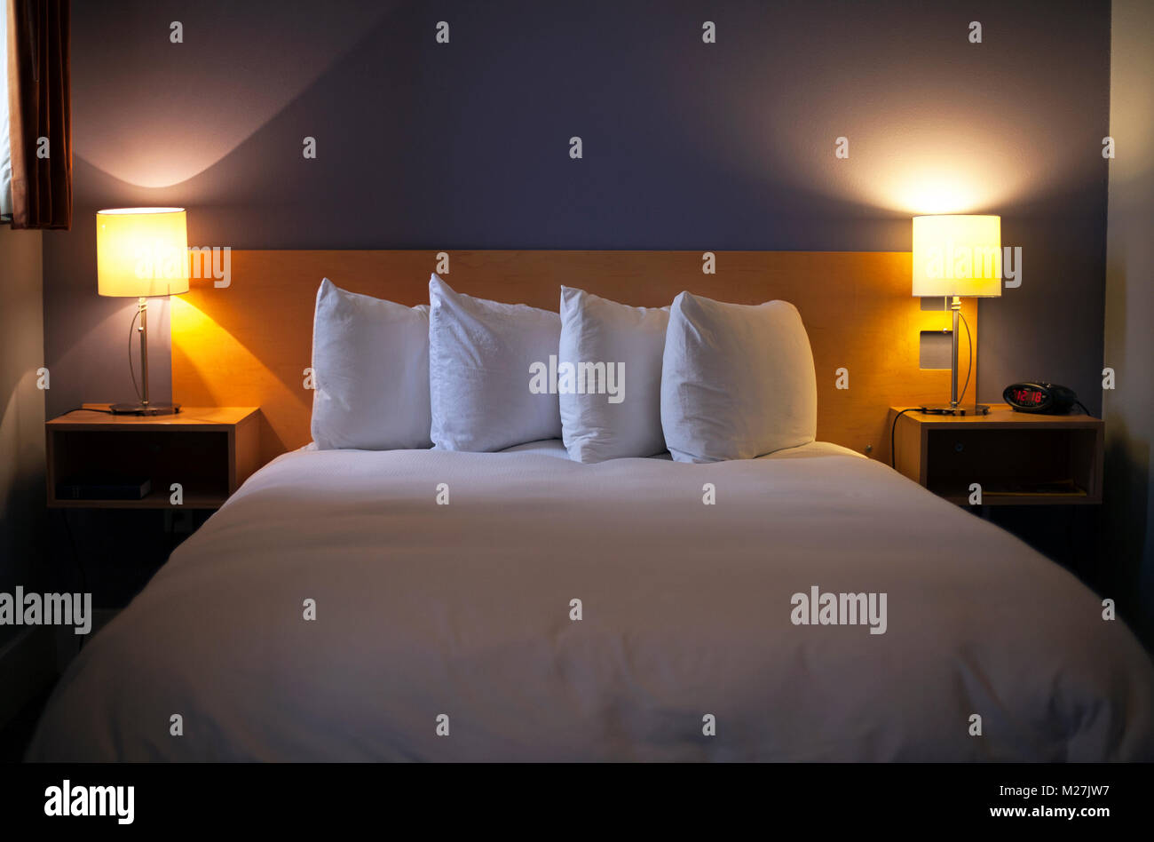 Soft light and arranged pillows are very inviting in a hotel room. - Stock Image